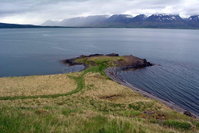 Costa hermosa del fiordo en la vanguardia de los picos nevosos en el oeste de Islandia fotos de archivo
