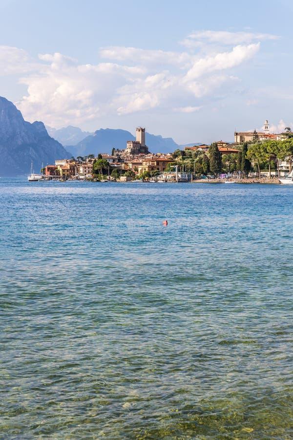 Costa idílico em Itália: Água azul e uma vila bonito em lago di garda, Malcesine imagem de stock