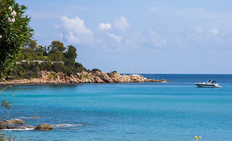 Costa italiana da rocha da praia da costa de mar de Sardinia da ilha da opinião do cenário e barco ancorado no sardegna de Arbata imagem de stock royalty free