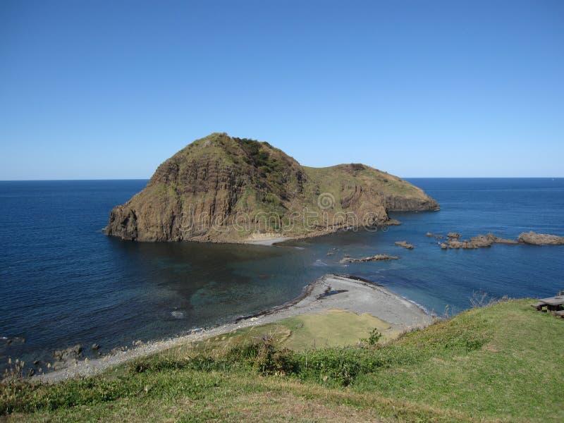 Costa japonesa de la playa con la isla rocosa y la agua de mar azul foto de archivo libre de regalías