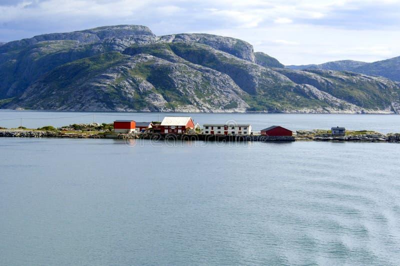 Costa norueguesa e pouco console com casas vermelhas fotografia de stock