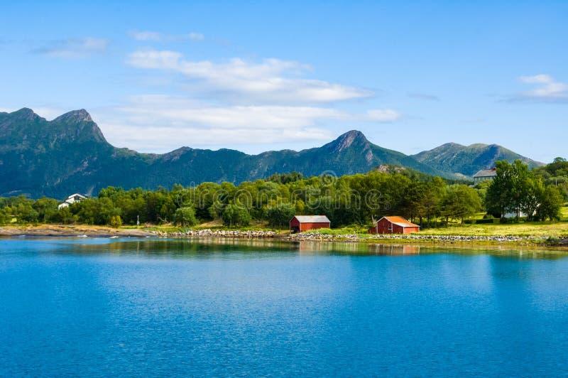 A costa norueguesa, paisagem típica no litoral norueguês com montanhas suporta dentro e casas vermelhas pequenas na costa imagem de stock royalty free