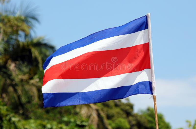 Costa Rica flag waving at Manuel Antonio national park beach in most beautiful beaches in the world, surfer beaches in America. Costa Rica flag waving at Manuel royalty free stock photos