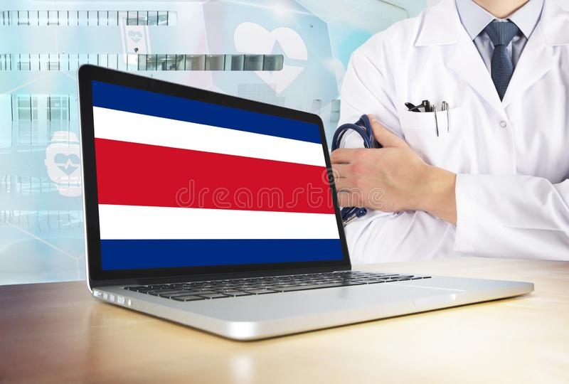 Costa Rica healthcare system in tech theme. Costa Rican flag on computer screen. Doctor standing with stethoscope in hospital. stock photography