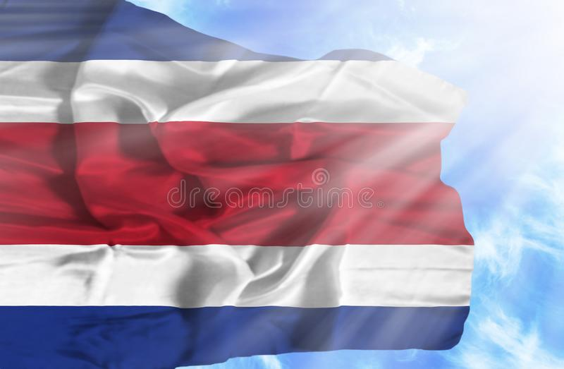 Costa Rica waving flag against blue sky with sunrays stock illustration
