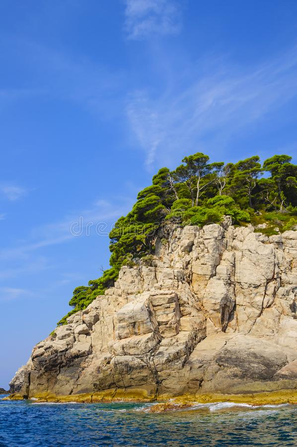 Costa rocciosa del mare adriatico, degli alberi verdi, del cielo blu e di chiara acqua di mare La Croazia, Europa fotografie stock