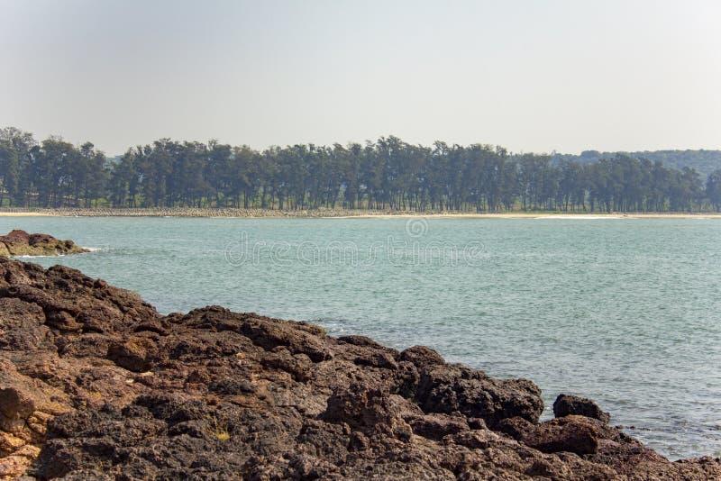 Costa rochosa contra a baía e o Sandy Beach do mar com árvores coníferas e uma barreira do tsunami dos tetrapods foto de stock royalty free