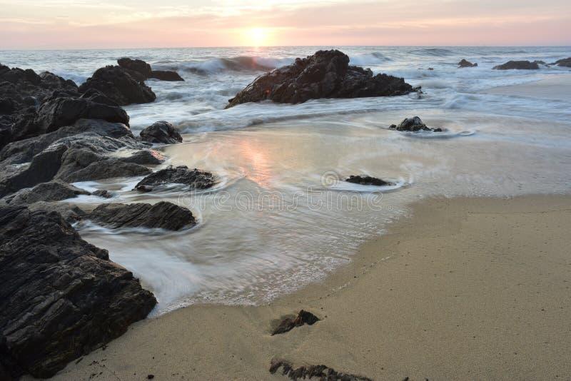 Costa rochosa do Oceano Pacífico do por do sol com as ondas na costa foto de stock