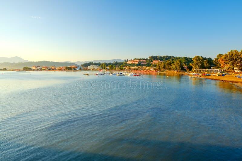 Costa costa rocosa hermosa en sorprender el mar jónico azul en la salida del sol en pueblo del día de fiesta de Sidari en la isla imagenes de archivo