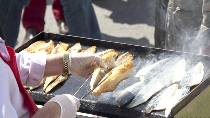 COSTANTINOPOLI - 2 MAGGIO: Le vendite turche dell'uomo grigliate pescano ai turisti a Eminonu il 2 maggio 2014 a Costantinopoli M fotografia stock libera da diritti