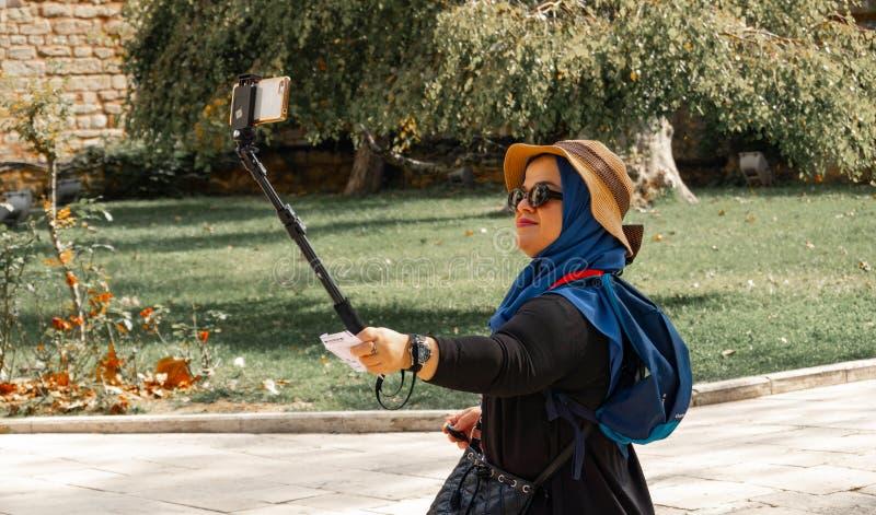 Costantinopoli, Turchia, settembre 2018: La giovane donna asiatica leggermente di peso eccessivo con il cappello di paglia e gli  fotografia stock
