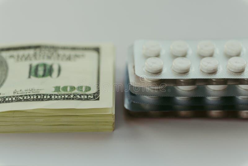 Coste de atención sanitaria, concepto costoso del tratamiento médico Paquete de dólares americanos y paquete de drogas fotos de archivo libres de regalías