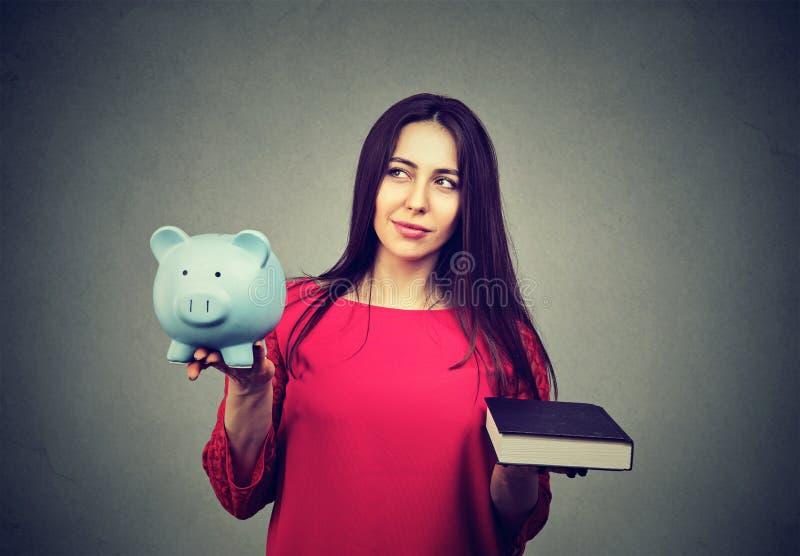 Coste de educación universitaria Hucha de equilibrio y libro de la mujer pensativa imágenes de archivo libres de regalías