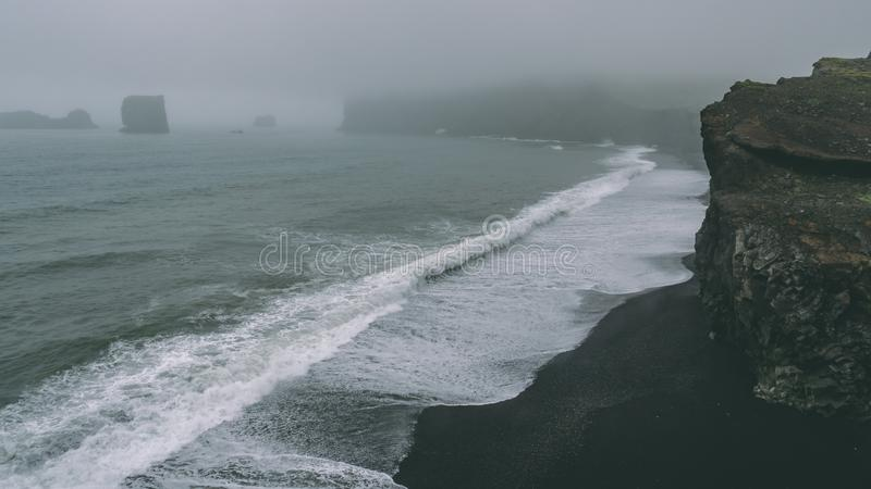Costee con la playa negra de la arena y las ondas grandes Costas costas de niebla foto de archivo