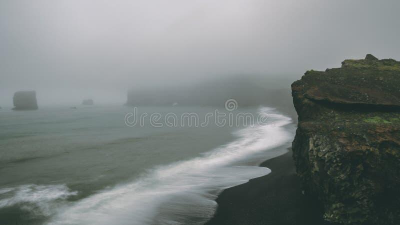 Costee con la playa negra de la arena y las ondas grandes Costas costas de niebla fotos de archivo libres de regalías