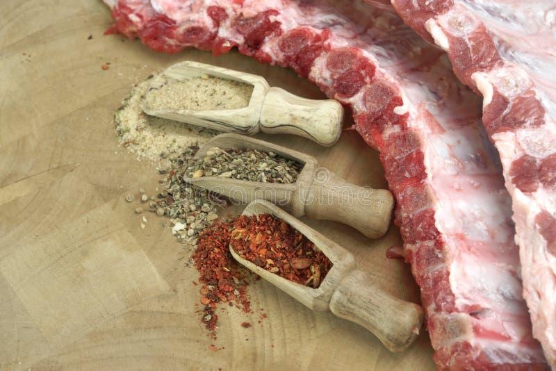 Costeleta crua dos reforços de carne de porco no close-up de madeira da placa fotografia de stock royalty free