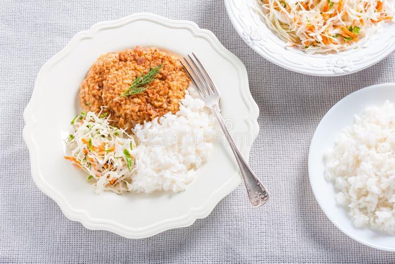 Costeleta de carne de porco com arroz e salada de repolho imagens de stock