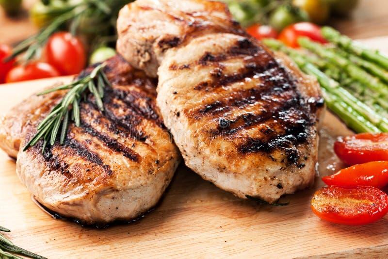A costeleta de carne de porco grelhada com alecrins folheia na placa de madeira fotografia de stock royalty free