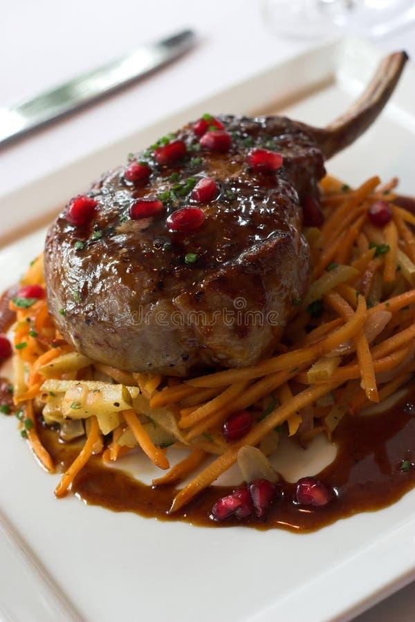 Costeleta de carne de porco na cama das cenouras fotos de stock royalty free