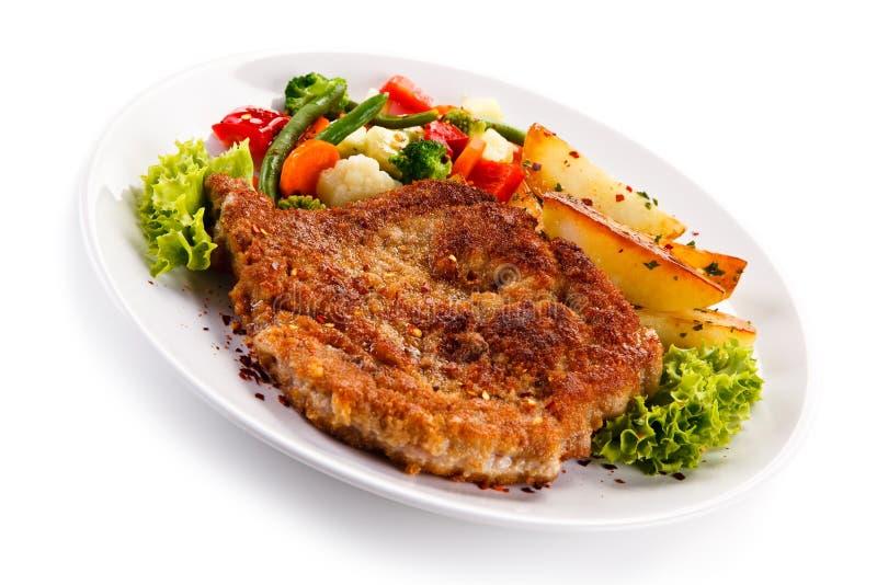 Costeleta de carne de porco fritada com batatas e os vegetais cozidos fotografia de stock royalty free