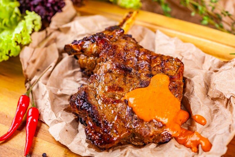 Costeleta de carne de porco grelhada com especiarias e ervas no papel de pergaminho fotos de stock