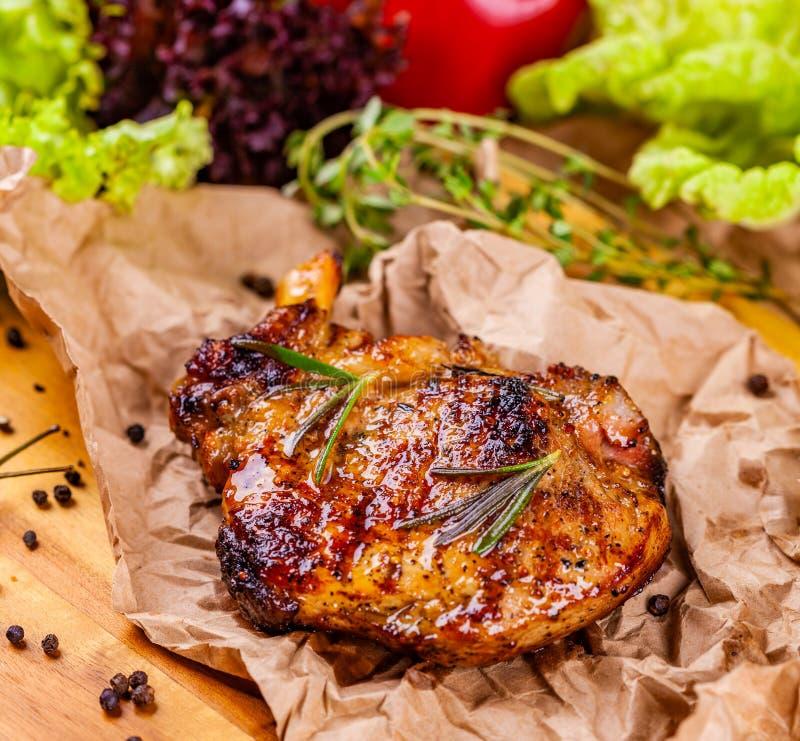 Costeleta de carne de porco grelhada com especiarias e ervas no papel de pergaminho foto de stock royalty free