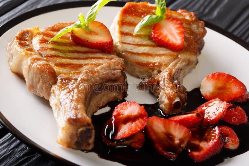 Costeleta de carne de porco saboroso grelhada quente com close-up balsâmico da morango sobre imagens de stock