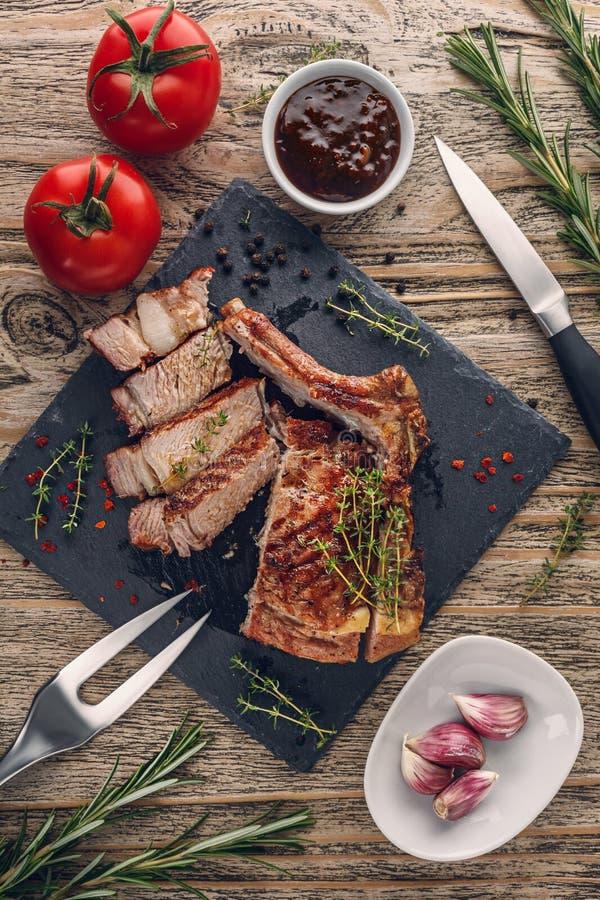 Costeleta de vitela grelhada cortada com os vegetais na tabela rústica imagens de stock