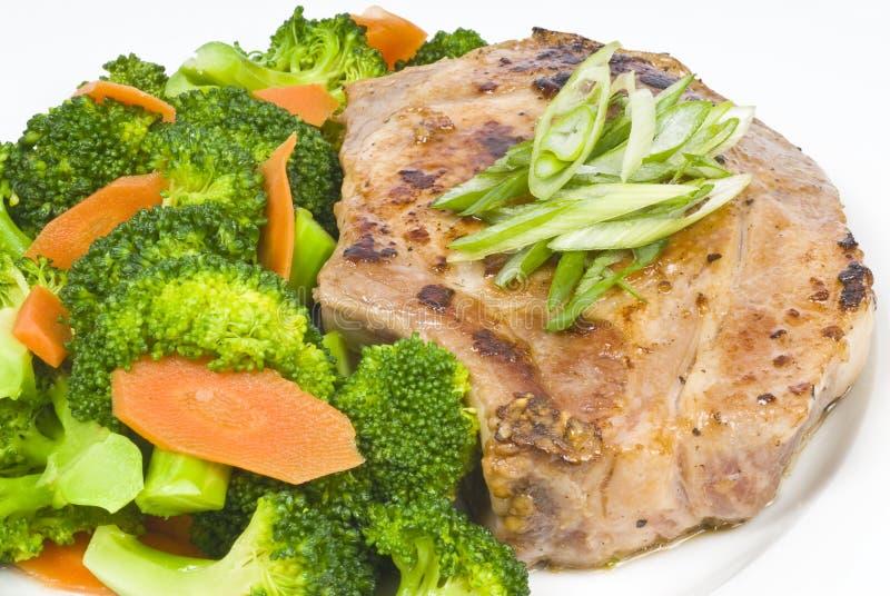 Costeleta e bróculos de carne de porco do alho imagem de stock royalty free