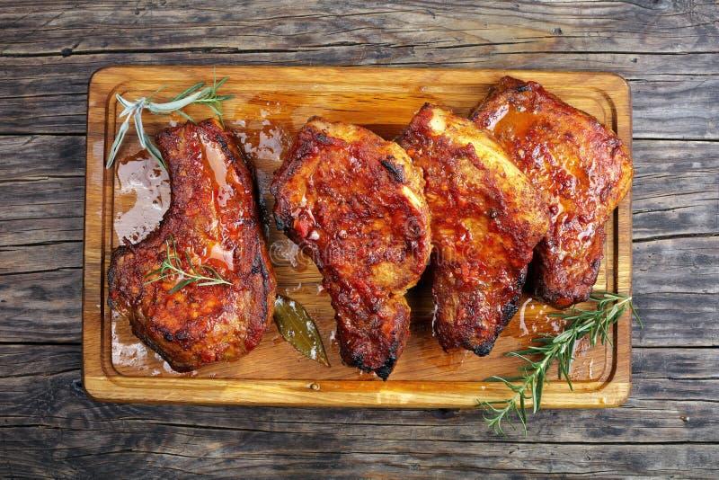 Costeletas de carne de porco suculentas em uma placa de madeira imagens de stock