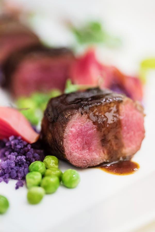 Costeletas de cordeiro com a ervilha batatas roxas fotografia de stock