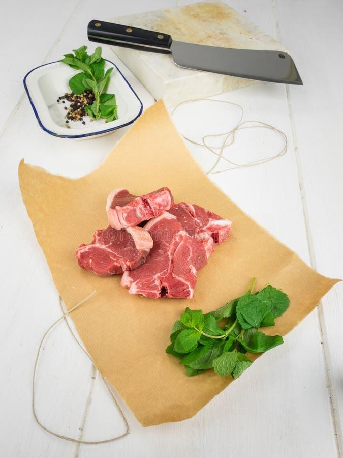 Costeletas de cordeiro com a hortelã no papel marrom com utensílios atrás fotografia de stock royalty free