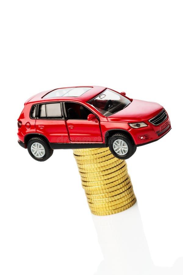 Costi automobilistici crescenti. automobile sulle monete immagini stock