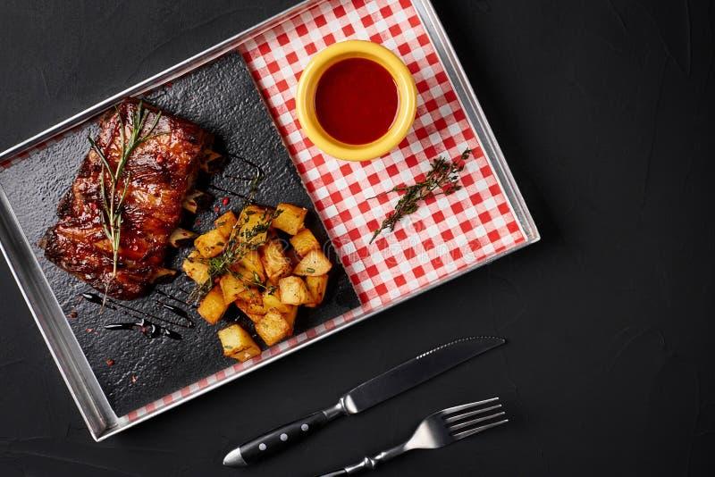 Costillas asadas a la parilla con la patata y la salsa cocidas del chile picante imagen de archivo