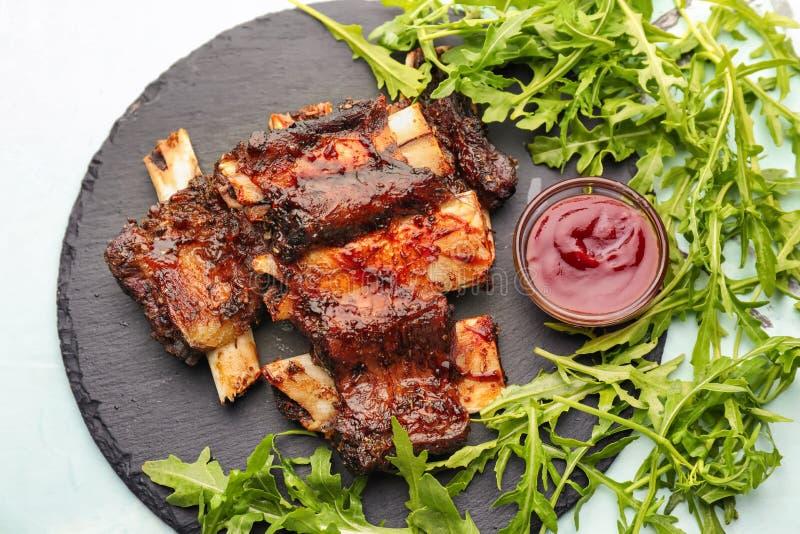 Costillas asadas a la parrilla deliciosas con la salsa y el arugula en la placa de la pizarra foto de archivo