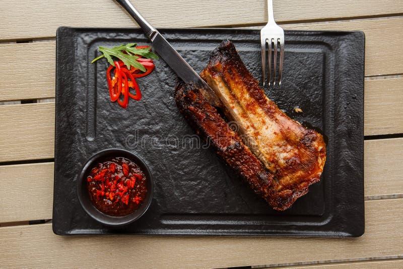 Costillas calientes asado a la parrilla y de la barbacoa de cerdo con pimienta de chiles calientes y salsa caliente en fondo de p fotos de archivo libres de regalías
