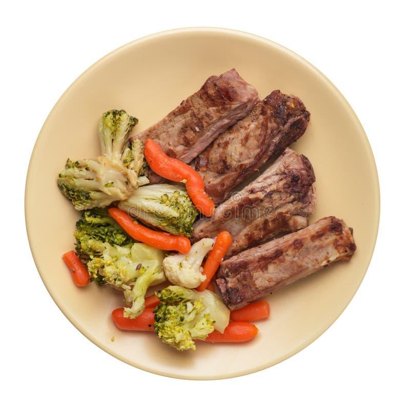 Costillas de cerdo asadas a la parrilla con la col, las zanahorias y el ajo del bróculi en una placa costillas fritas con las ver fotos de archivo