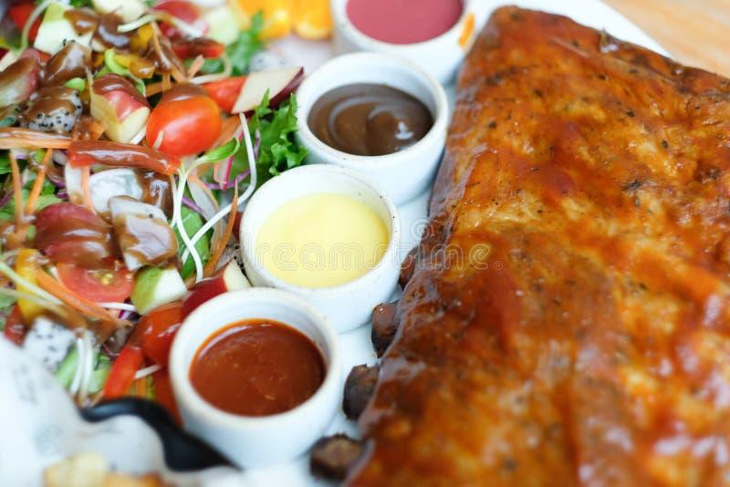 Costillas de cerdo asado con la salsa de barbacoa y la ensalada de fruta foto de archivo
