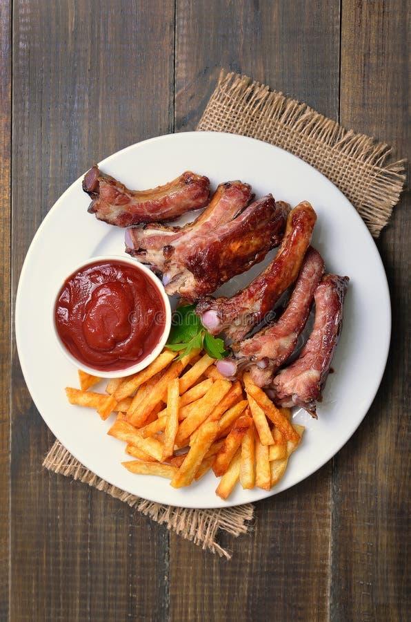 Costillas de cerdo, fritadas y salsa de tomate fritas, visión superior de la patata foto de archivo libre de regalías