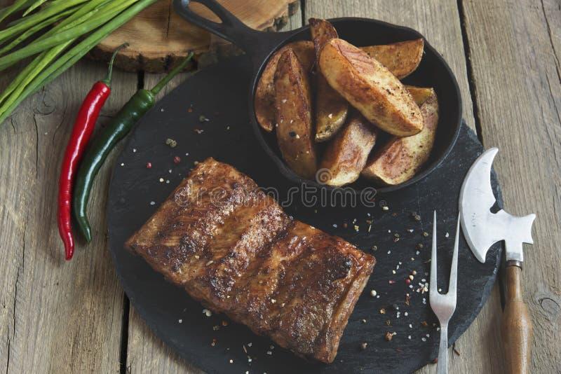 Costillas de cerdo fritas con las patatas y las especias