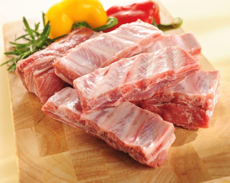 Costillas de cerdo sin procesar. Arreglo en una tarjeta de corte. imágenes de archivo libres de regalías