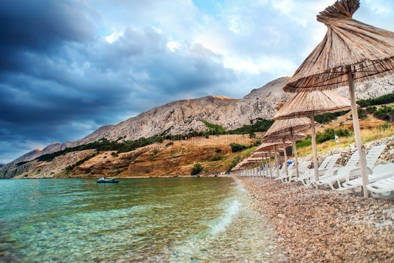 Costline di Rocky Adriatic Sea con gli ombrelli della paglia, i sunbends e chiara acqua Paesaggio del mare, località di soggiorno fotografie stock libere da diritti