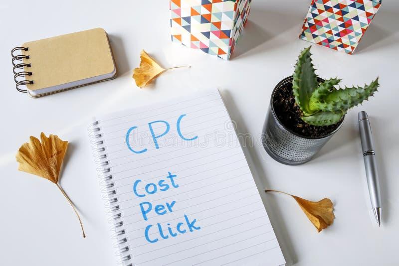 Costo di CPC per clic scritto in taccuino fotografia stock