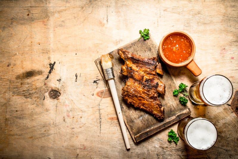 Costole affumicate del barbecue con salsa al pomodoro e birra fredda fotografia stock