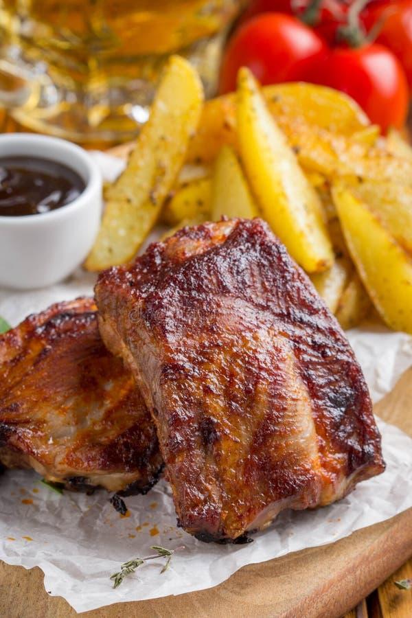 Costole arrostite della carne con le fette fritte della patata con salsa barbecue, immagine stock