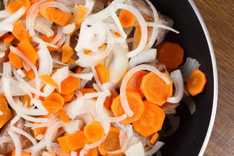 Costole arrostite della carne di maiale con le carote e le cipolle su una padella immagine stock libera da diritti
