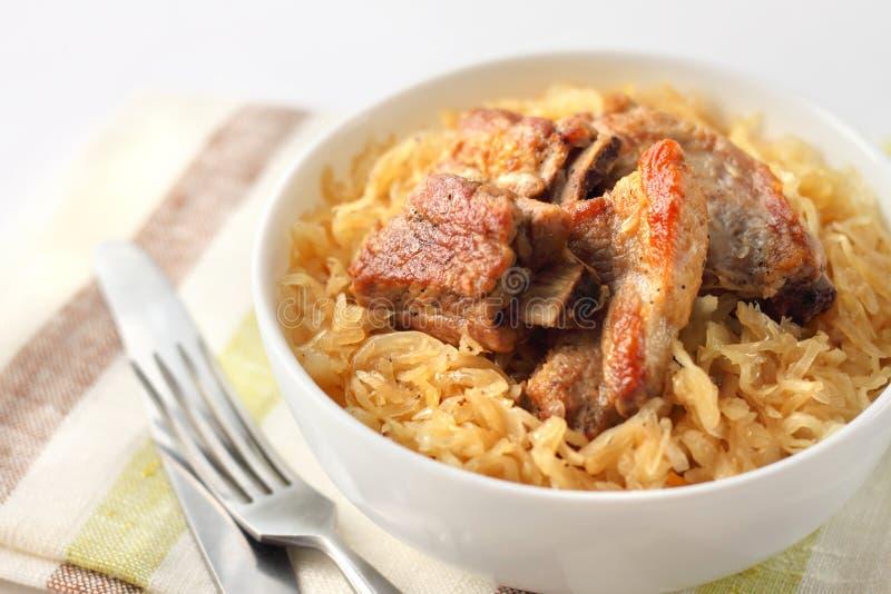 Costole di carne di maiale al forno con i crauti fotografia stock