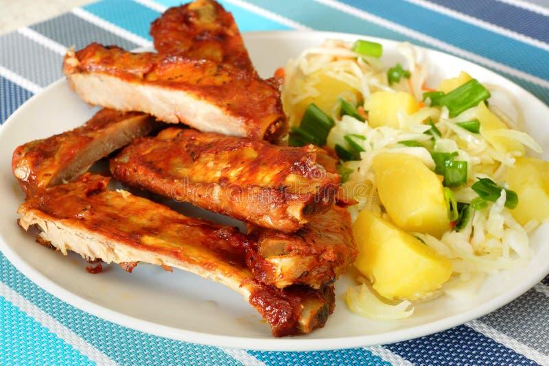 Costole di carne di maiale al forno con l'insalata di patata immagini stock libere da diritti