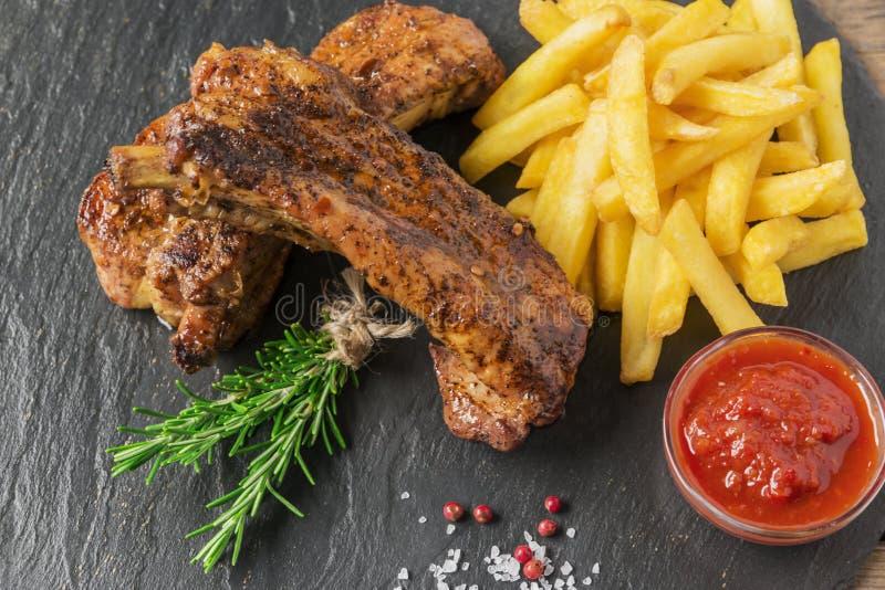 Costole di carne di maiale al forno con le patate fritte e la salsa rossa fotografia stock libera da diritti