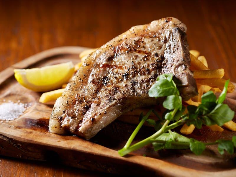 Costole di carne di maiale arrostite deliziose con il limone e le erbe sul cutti di legno fotografia stock
